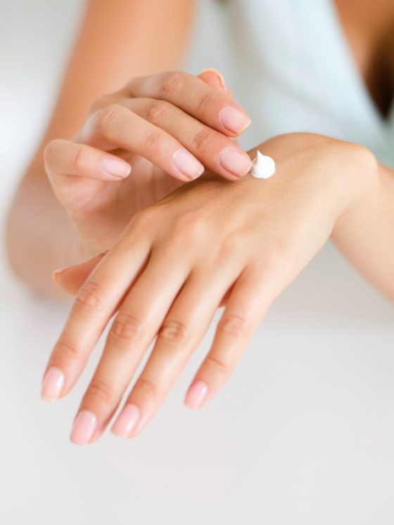 Woman applying lotion to her hands