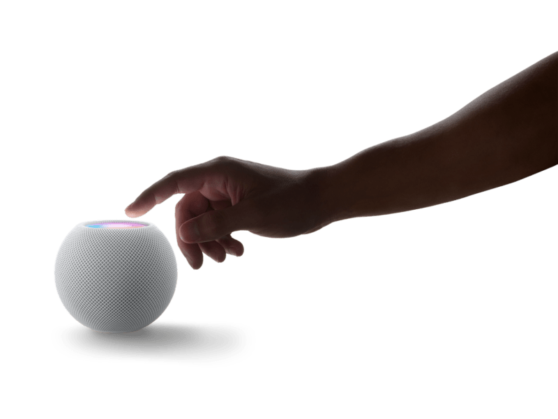 HomePod Mini: Hand reaching out toward unit